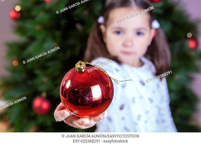 Little girl shows a ball for Xmas Tree decoration
