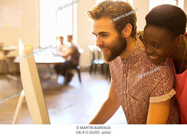 Smiling casual business people sharing computer in office