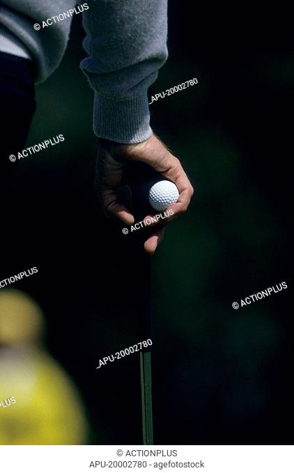 Close up of a golfer holding his club and a golf ball in one hand