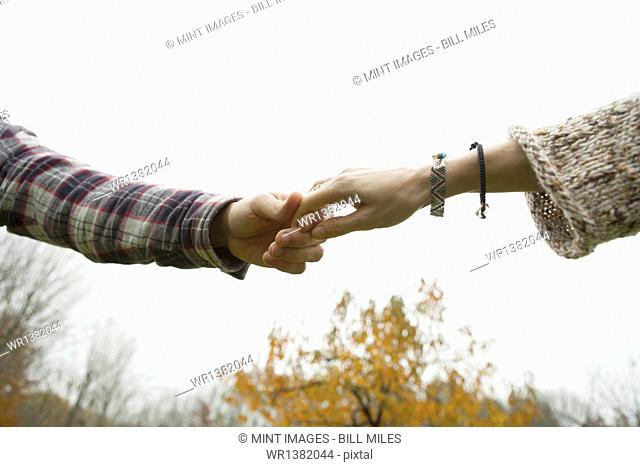 Two people holding hands, a couple outdoors