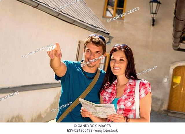Young couple in city man pointing direction