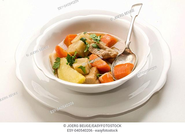 classic home made irish stew in a white bowl with home growen vegetable