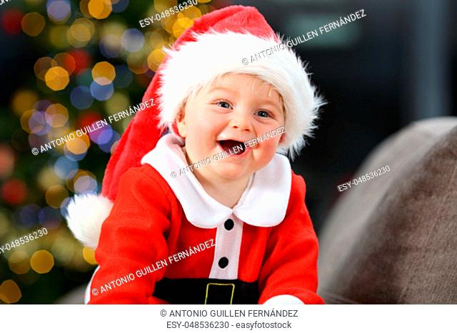 Cheerful baby dressed as santa claus in christmas