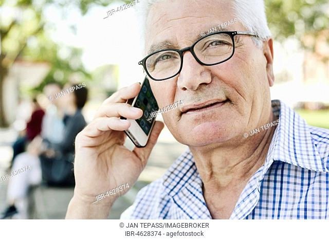 Grey-haired senior with glasses talking on the phone with his smartphone, Germany