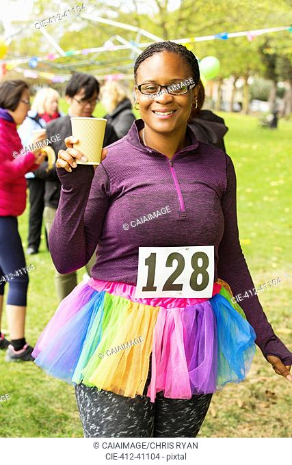 Portrait smiling female runner in tutu drinking water at charity run in park