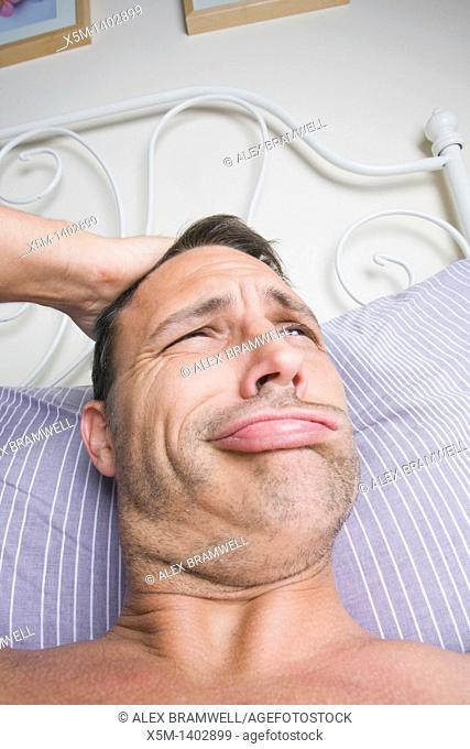 Man in his bedroom waking up and scratching his head