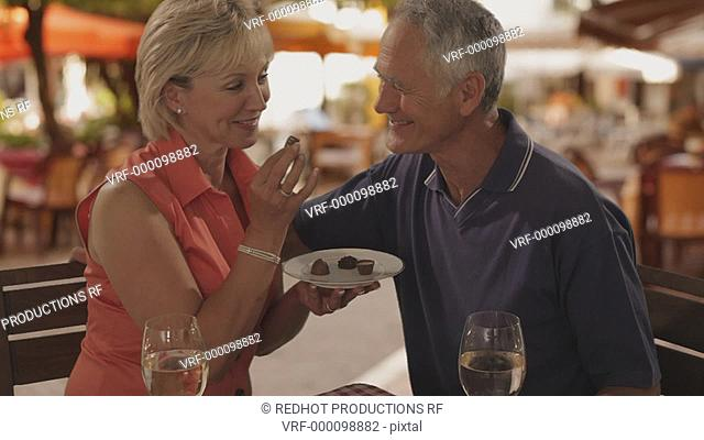 senior couple at cafe in town woman feeding man