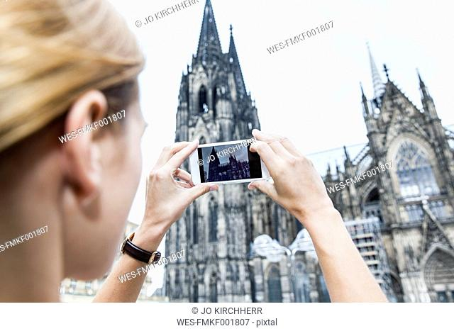 Germany, Cologne, young woman taking a picture of Cologne Cathedral with smartphone
