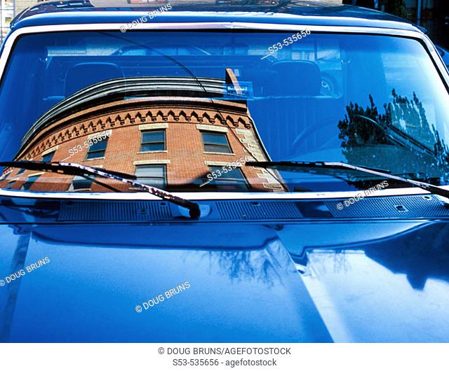 Brick building reflected in windshield in blue car