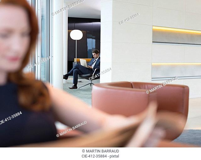 Business people using laptop and reading newspaper in lounge