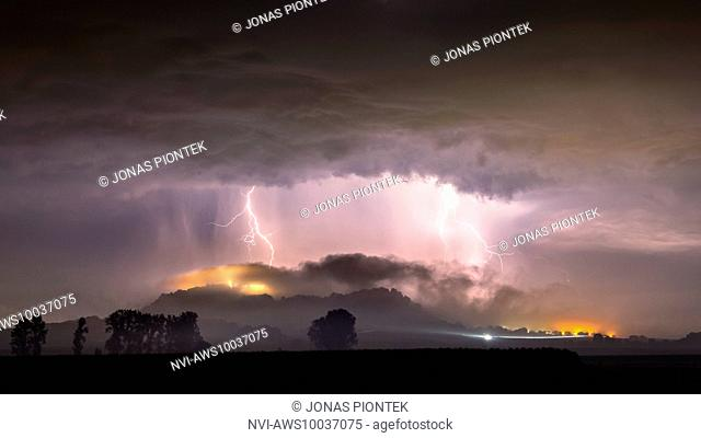 Strong cloud-to-ground lightnings behind the foggy mountain of Amöneburg, Hessia, Germany