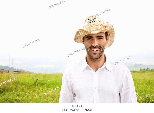 portrait of young man standing in meadow