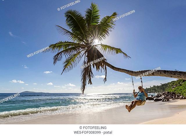 Seychelles, La Digue, Anse Fourmis, beach with palm and tourist on swing