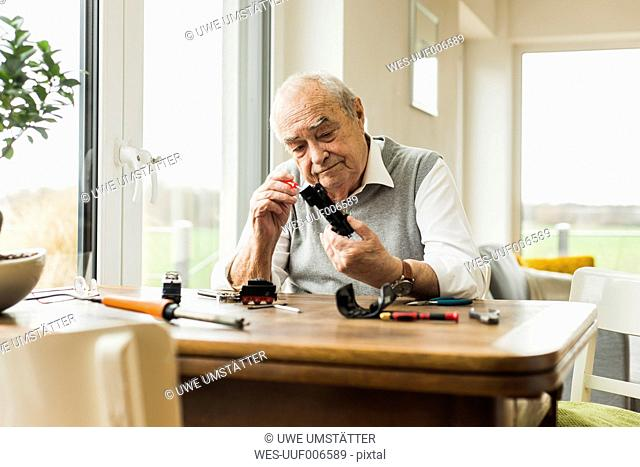 Senior man repairing toy train at home