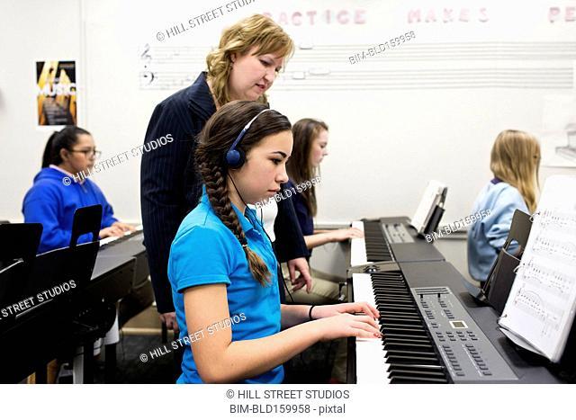 Teacher helping student practice keyboard in high school band class