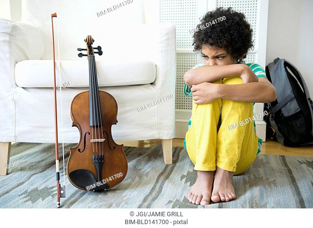 Angry mixed race boy refusing to practice violin