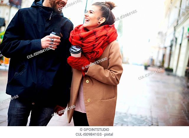 Couple with disposable cups holding hands