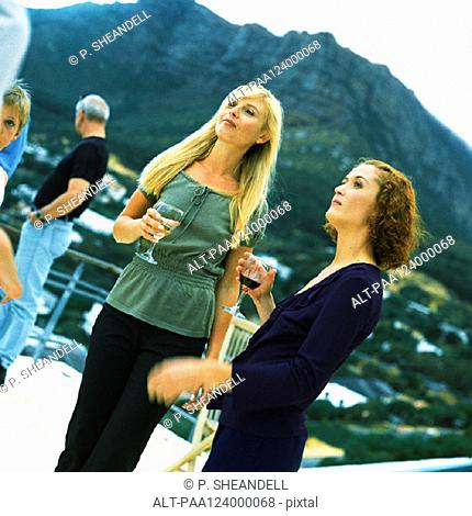 People standing and holding glasses, outside, mountain in background