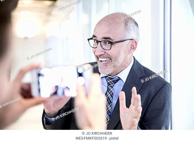 Businessman posing while woman taking picture of him with smartphone
