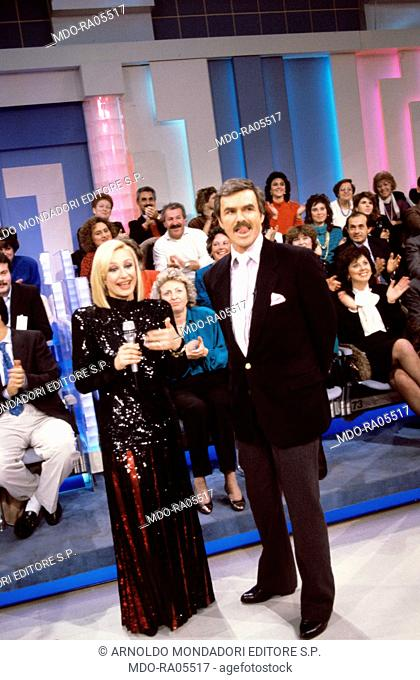 Italian showgirl Raffaella Carrà (Raffaella Maria Roberta Pelloni) interviewing American actor Burt Reynolds in a Tv show. 1989