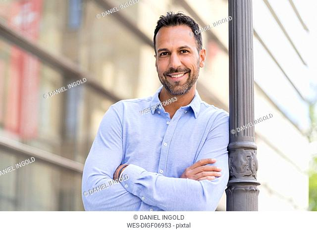 Portrait of confident businessman leaning against a lamppost in the city