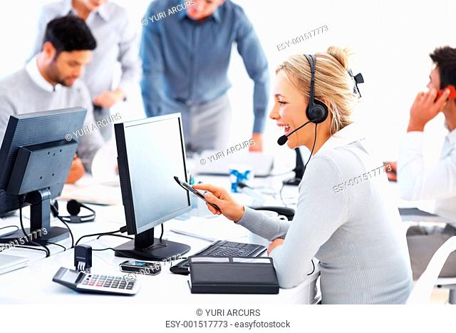 Beautiful call center representative talking on headset and working on computer