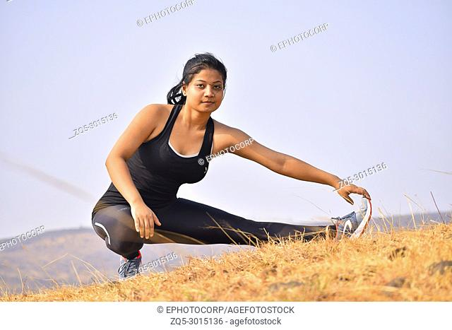 Young Indian girl doing fitness exercise. Mountain backdrop, Pune, Maharashtra