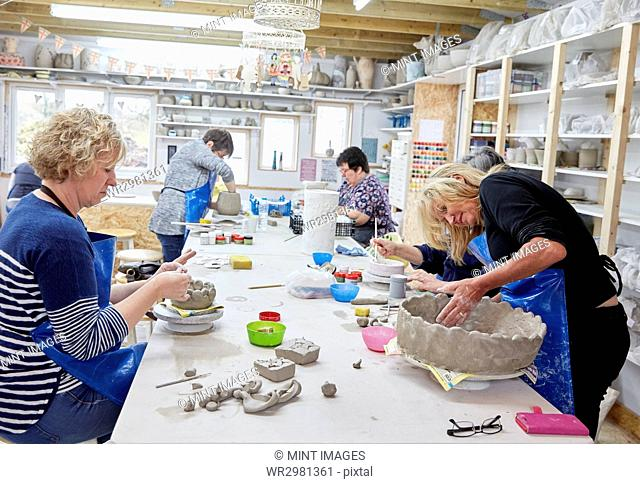 Five people, women in a pottery studio, working on handbuilding clay objects