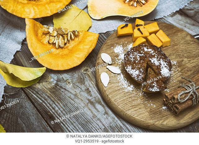 fresh pieces of pumpkin and pumpkin cake on a wooden board, empty space in the middle