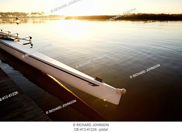Scull at dock on tranquil sunrise lake