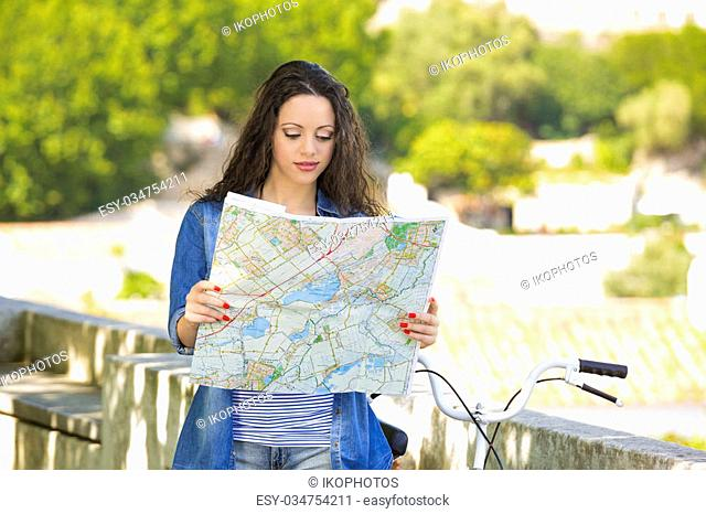 A young and beautiful female tourist searching a place on the map