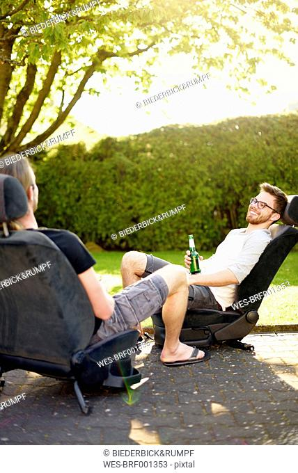 Two young men sitting on removed car seats drinking beer