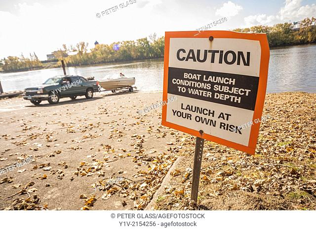 Sign by a river cautioning people who are launching boats
