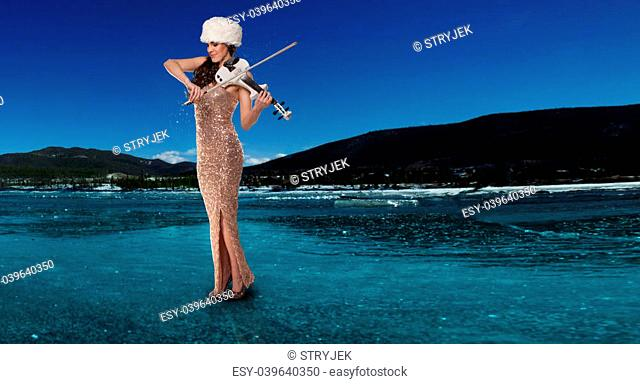 Beautiful panoramic view of an attractive elegant young woman playing a violin on a frozen winter lake in Rocky Mountains, Colorado on a sunny day