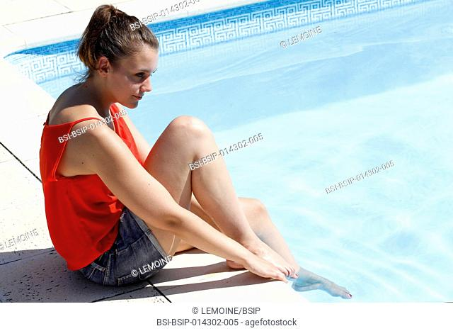 A young woman sitting on the edge of a swimming pool with her feet in the water