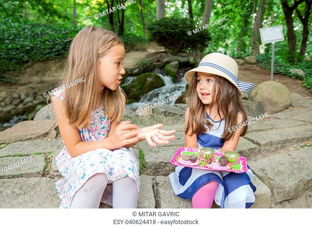 Two little girls at picnic in park, playing in nature
