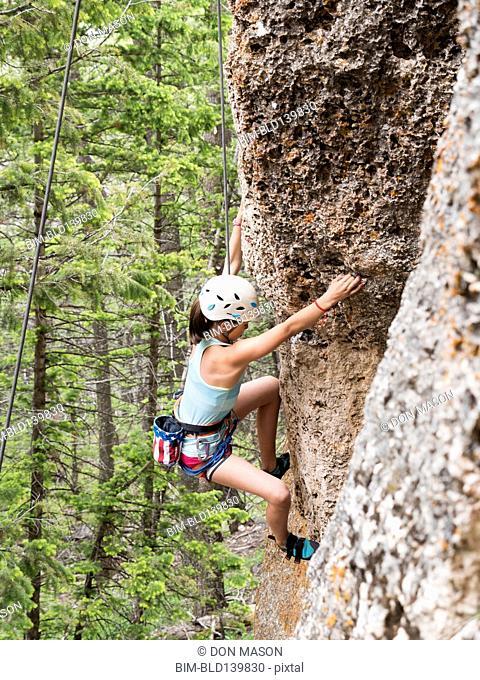 Mixed race girl climbing steep cliff