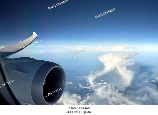 Aircraft turbo prop jet engine and wingtip in flight with blue sky and white cumulonimbus clouds