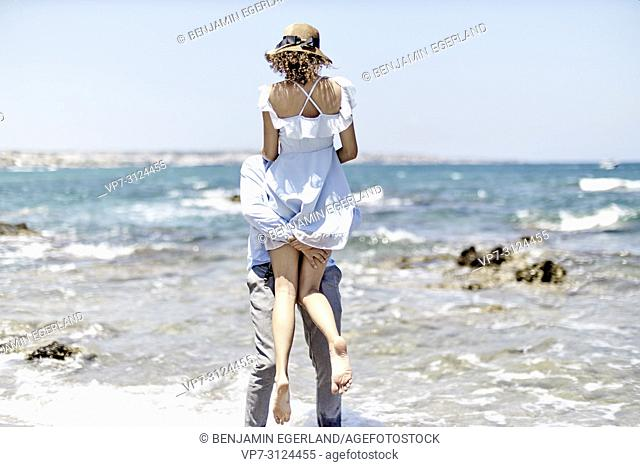 man carrying woman at beach, love, couple, dating, honeymoon, in Hersonissos, Crete, Greece
