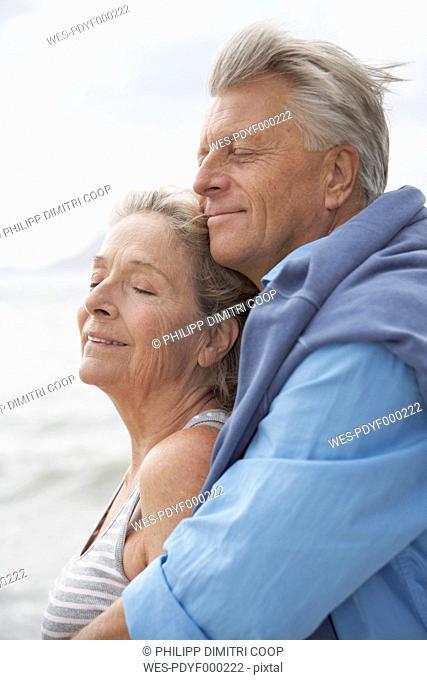 Spain, Senior couple on beach at Atlantic, smiling