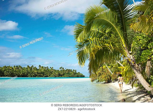 Aitutaki. Cook Island. Polynesia. South Pacific Ocean. A tourist walks along the edge of the palm-fringed beach in One Foot Island