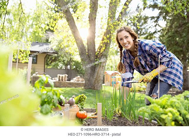 Smiling woman tending to vegetable garden
