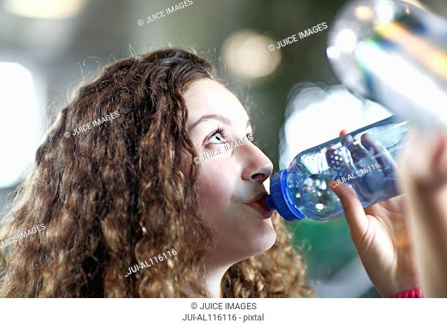 Teenage girl drinking from water bottle in gym