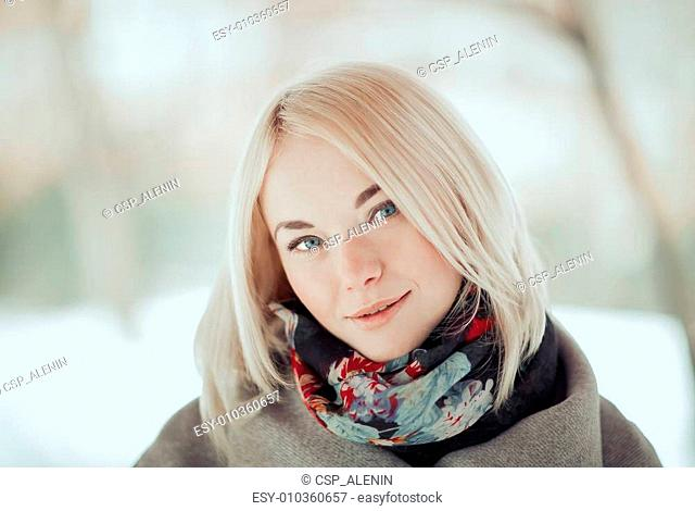 Portrait of the beautiful girl of the blonde with green eyes. Sunny winter day. Toned in warm colors