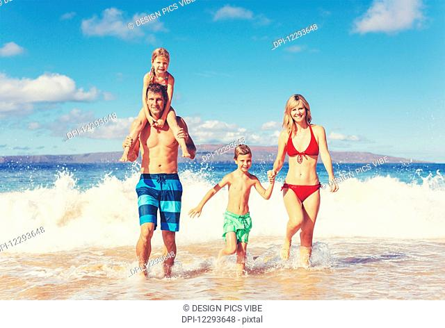 Happy family having fun on beautiful warm sunny beach