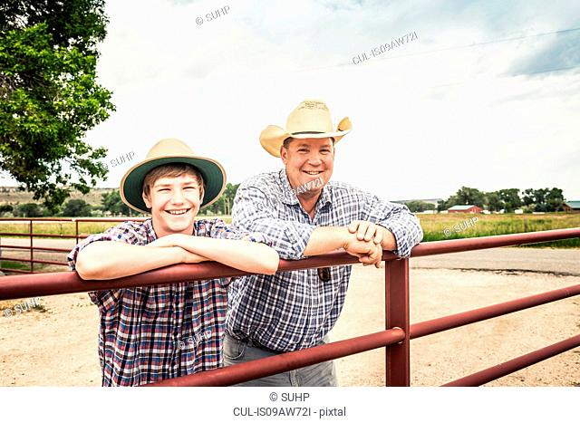 Portrait of farmer and teenage grandson leaning against gate