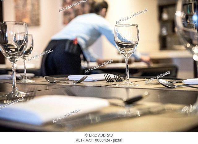 Woman setting restaurant table