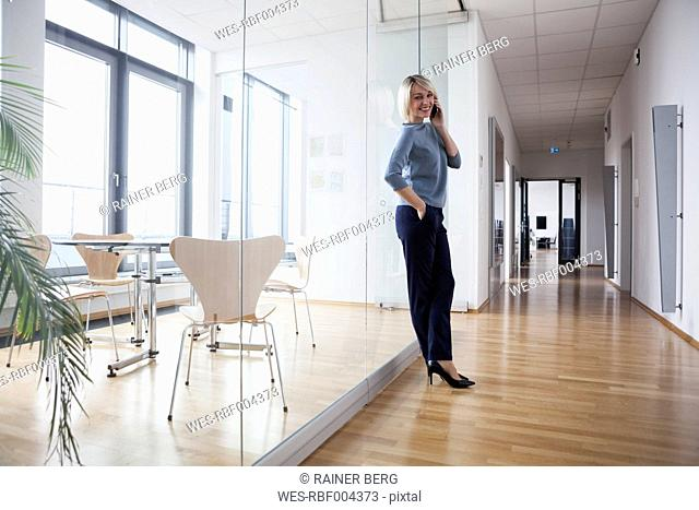 Businesswoman standing in office talking on the phone