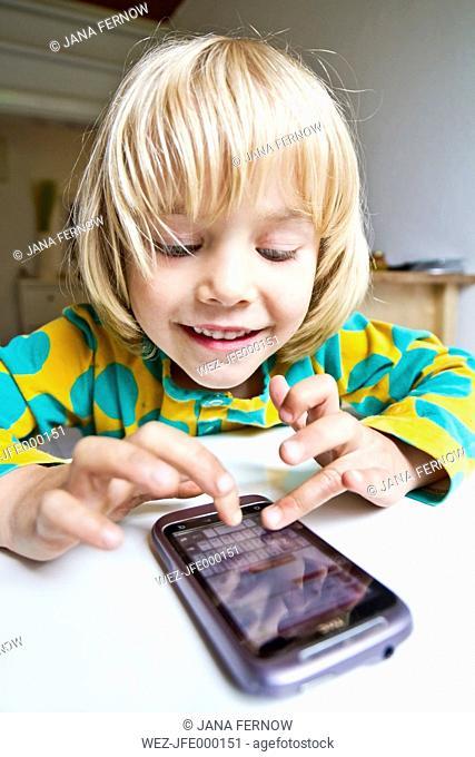 Germany, Kiel, Girl playing with smartphone