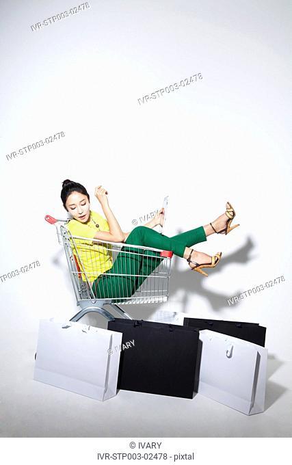Woman In A Shopping Trolley, Using Digital Tablet